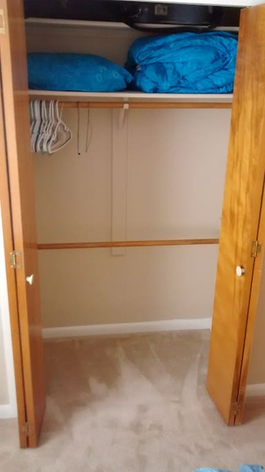 Large closet with clothes hanging space, room for suitcases on the floor, extra towels, blankets and pillows.