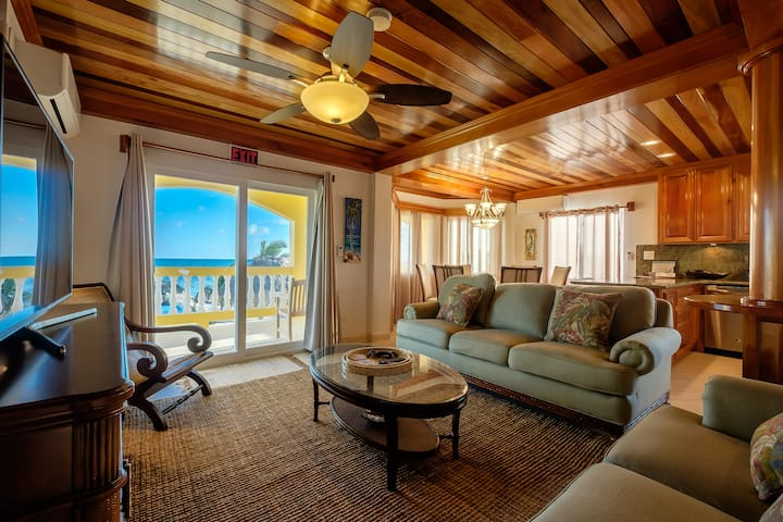 An open-concept living room, dining room and kitchen create an inviting main living area - oh, and the view of the Caribbean Sea isn't bad either!  The sofa is a queen-sized sleeper