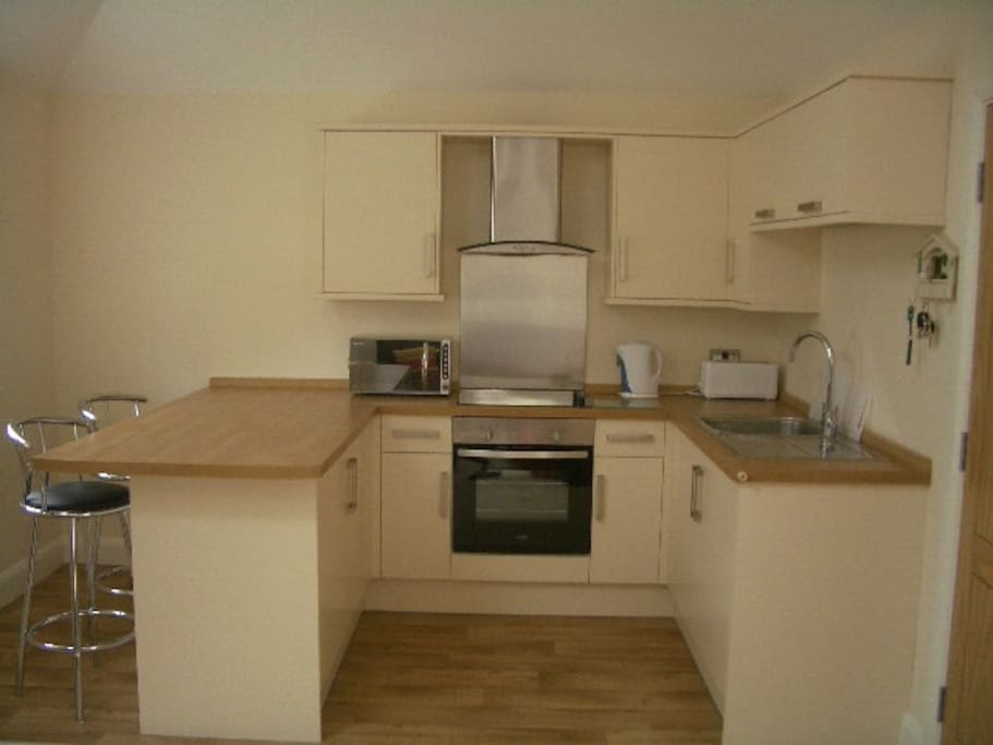 Open plan kitchen area with appliances and breakfast bar.