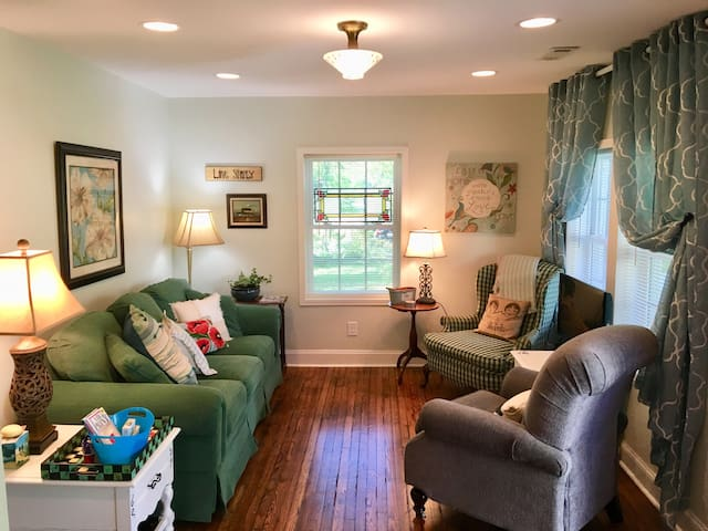 The comfy living room with recliner, side chair and 3-person sofa. TV sits between the chairs in front of the window, which looks out to Walnut Grove, an antebellum home across the street.