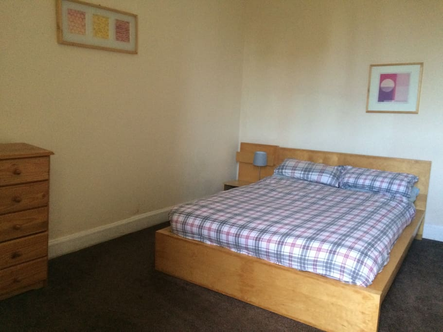 Bedroom with double bed, chest of drawers and wardrobe.