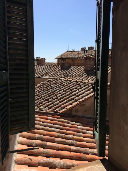 The beautiful terracotta roofs of Panicale from the shuttered master bedroom window. What a view!