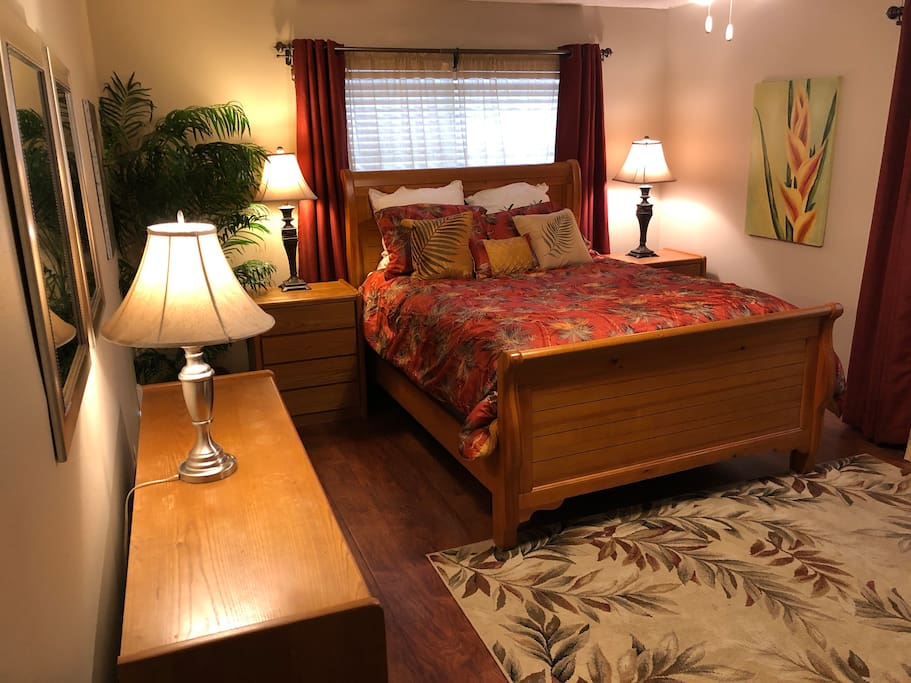 The master bedroom feature a beautiful sleigh bed in a tropical theme.