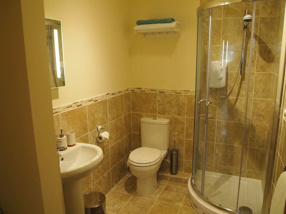 Bathroom with corner shower.  There is also a washing machine in here.