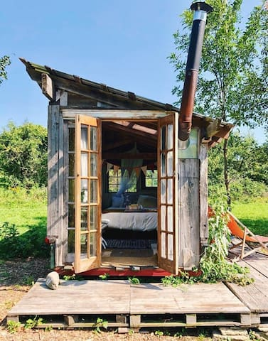 The caravan is the smallest and sweetest of our accommodations; a tiny home built by artist, Paul Jacobsen.  It holds a full size bed and is nestled in the orchard.