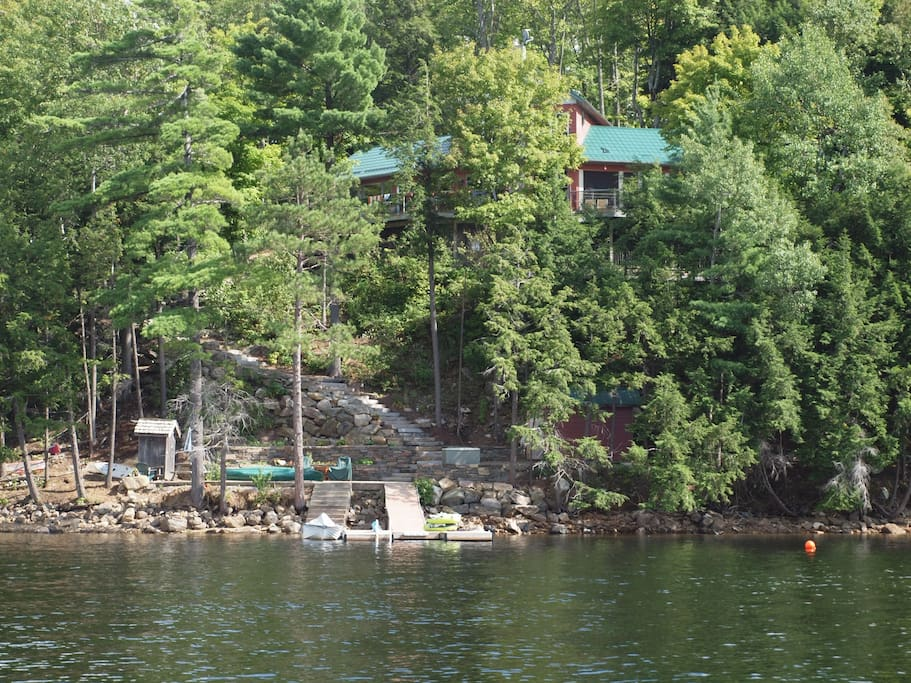 Summer view of the cottage from the lake -- its hard to see behind the trees.