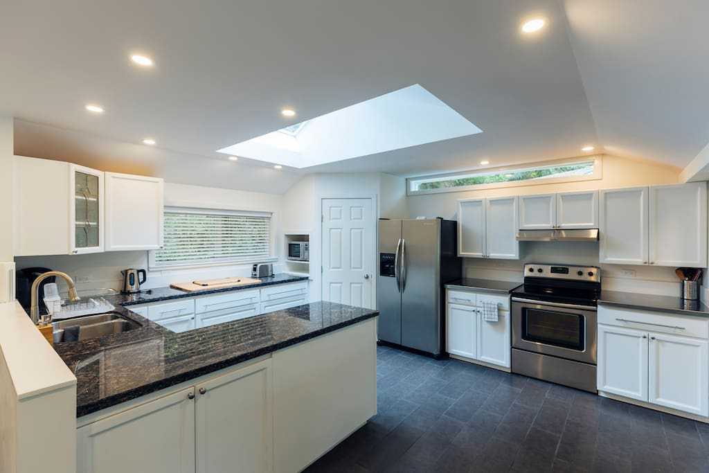 Sky-lit open concept kitchen with lots of cooking utensils, pots, pans and natural lighting