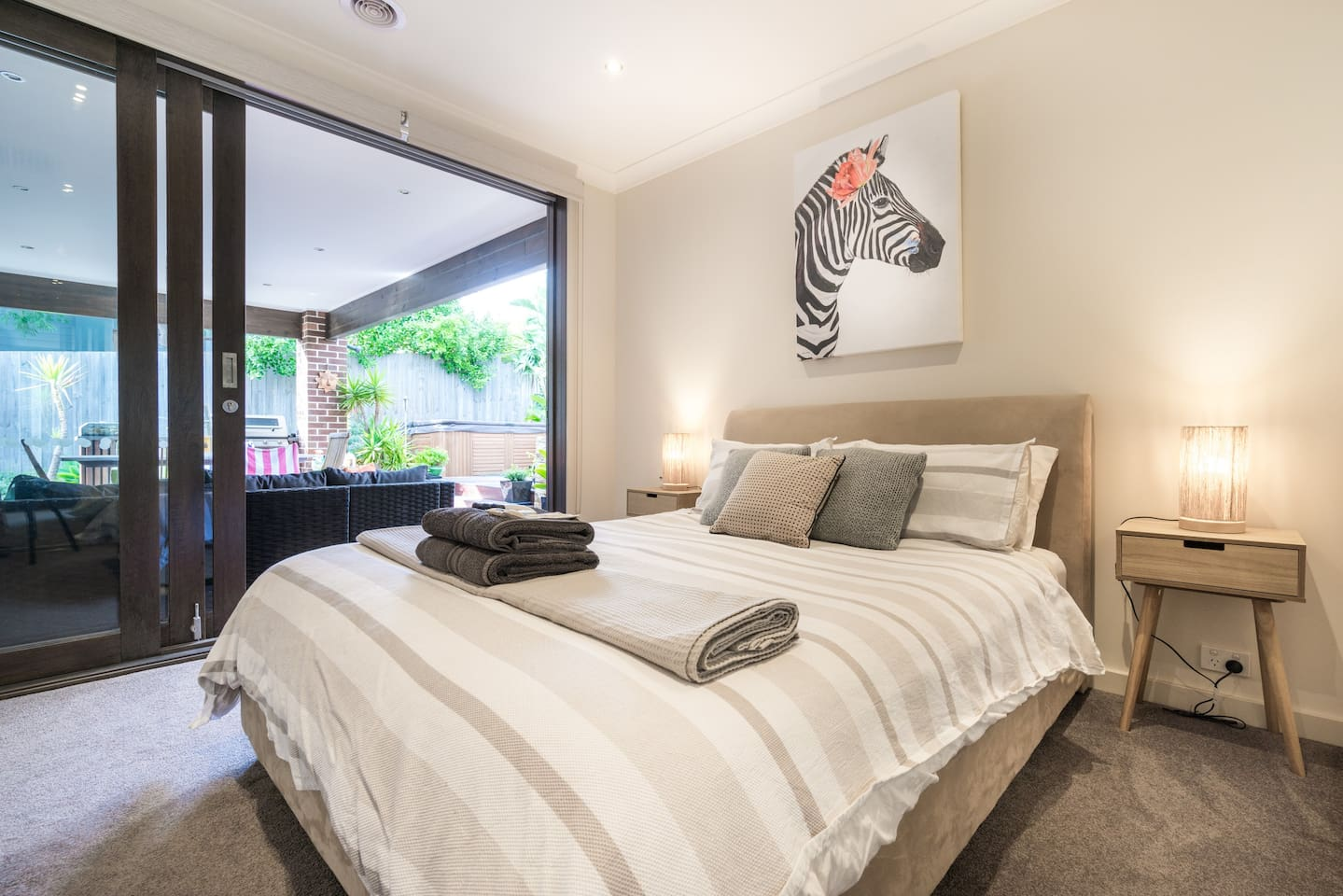 Main Queen bedroom looking onto the shared deck and lush garden
