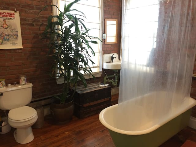 Shared bathroom with exposed brick, large claw foot tub, and great light. Towels are in the closet and shampoo, conditioner and body wash are provided.