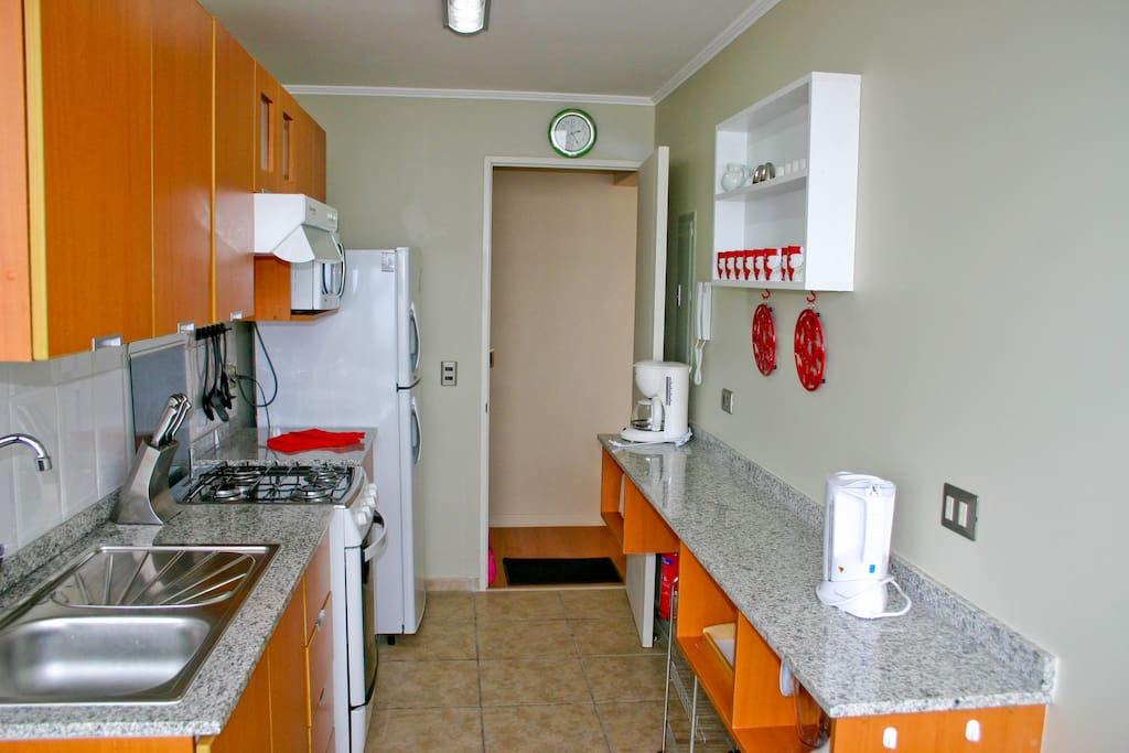 Fully equipped kitchen with table and chairs at one end, seaviews.