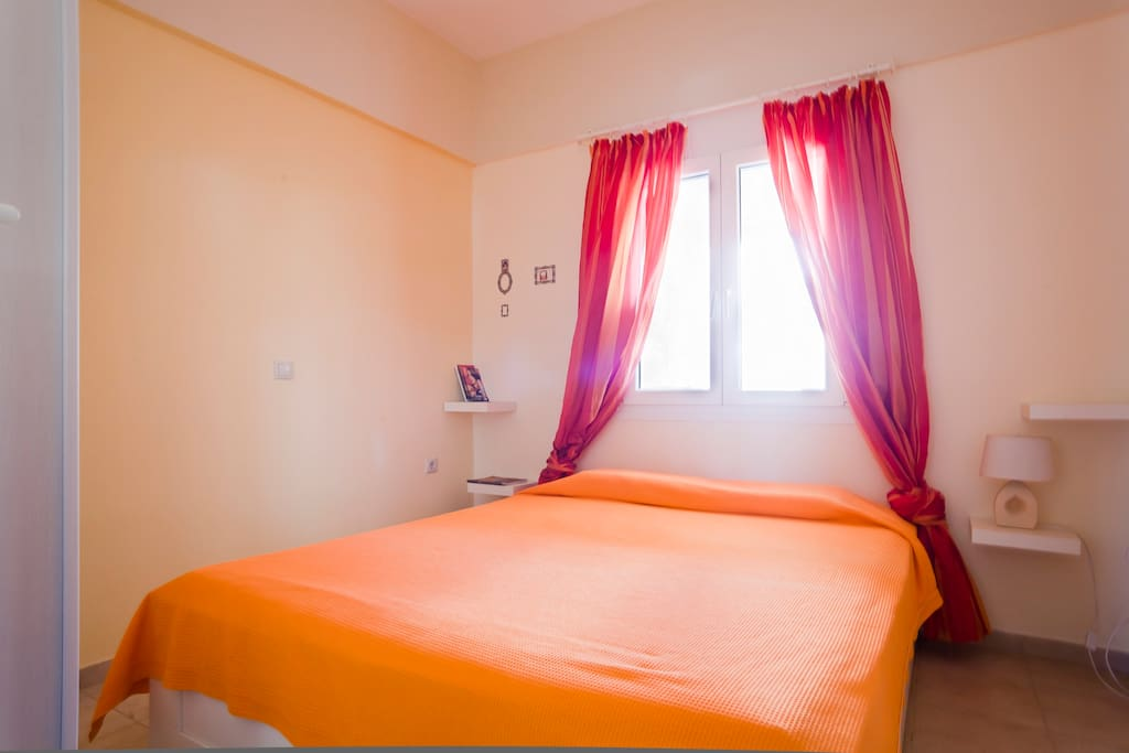 A large and sunny master bedroom with a large double bed.