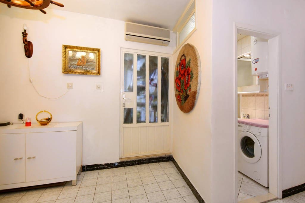 Hallway with small fridge, bathroom and entrance into two rooms, it is separate with door from the part where my grandmother lives