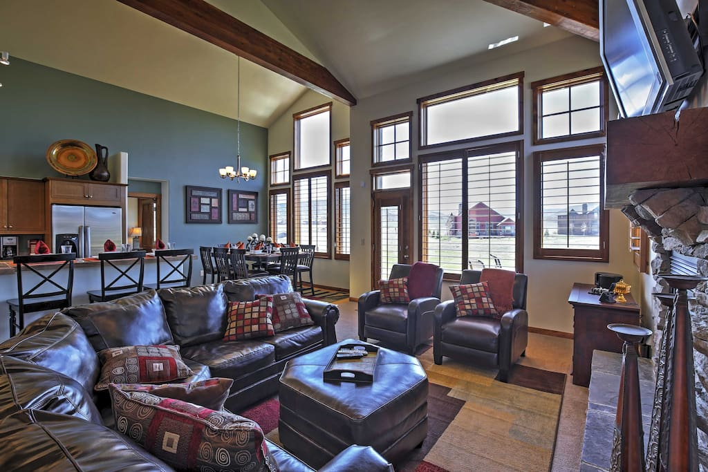 The interior features vaulted ceilings, floor-to-ceiling windows, and gorgeous wood accents for a homey feel.
