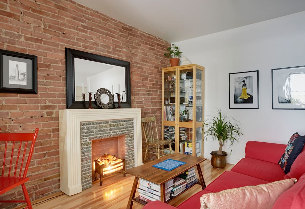 The brick wall and electric fireplace give it a super cozy feel