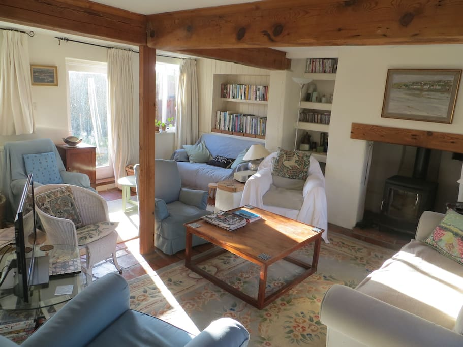 The living room has a comfy sofa, lots of chairs, TV with internet, woodburner and door to garden.