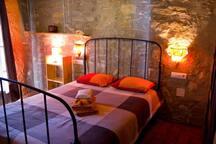 su cama con estilo y su piedra vista en pared