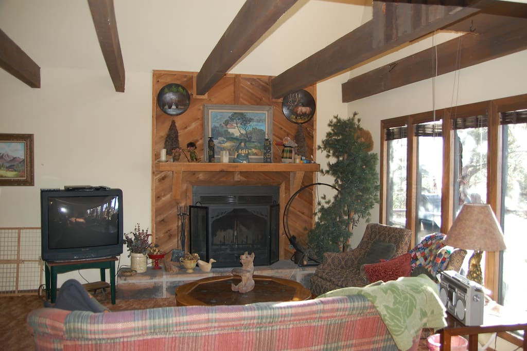 Living room on main floor with gas fireplace, tv and view of deck
