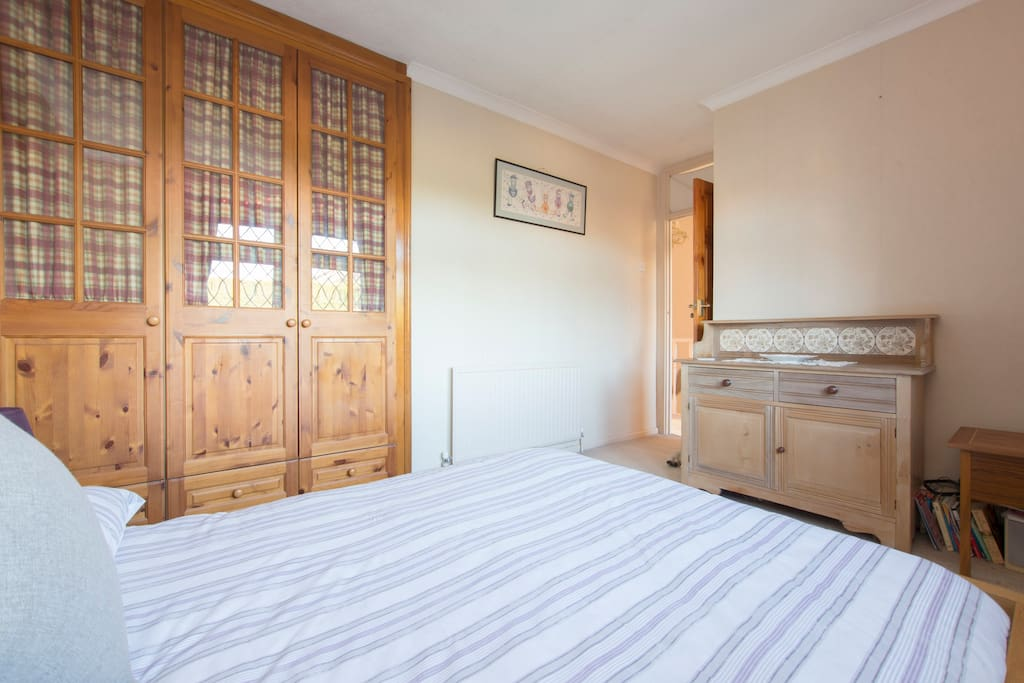 Spacious double bedroom with fitted wardrobe and chest of drawers