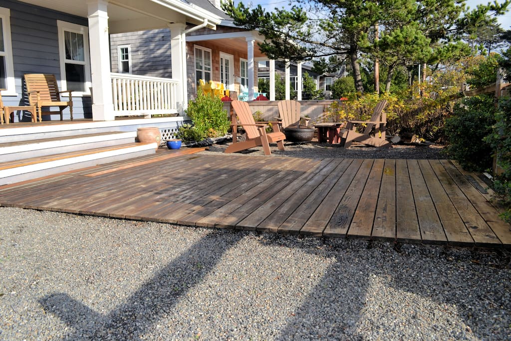 Front yard with large deck and gravel, 4 chairs, and a portable fire pit