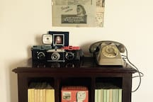 Old cameras and telephone on the small library
