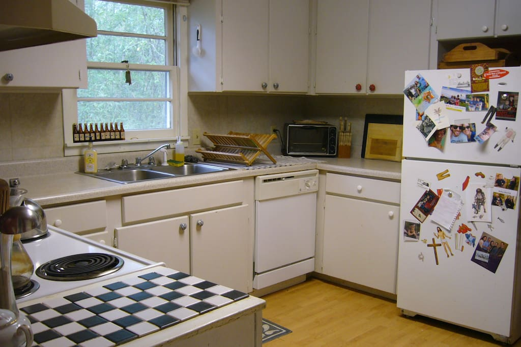 The kitchen.  Its clean and has colorful cabinet pulls.
