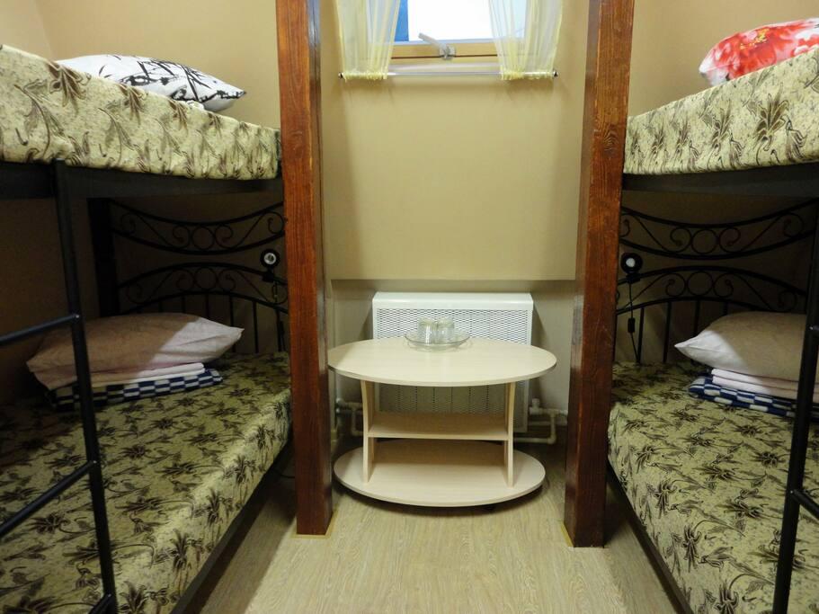 Вид одного из 4-х местных номеров с кондиционером и телевизором, шкафом. тумбами, стульями и столом.