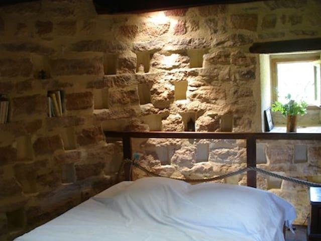 1er étage. Chambre ronde avec lit double. Boulins (anciens nids de pigeons) dans le mur en vieilles pierres.