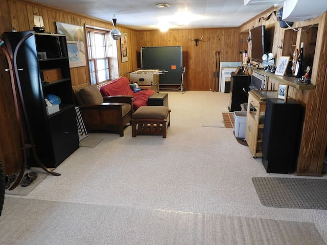 Classic Mid-century lower level living room with full size futon, TV, Stereo, bar, Foosball table, wood burning stove and of course a disco light.