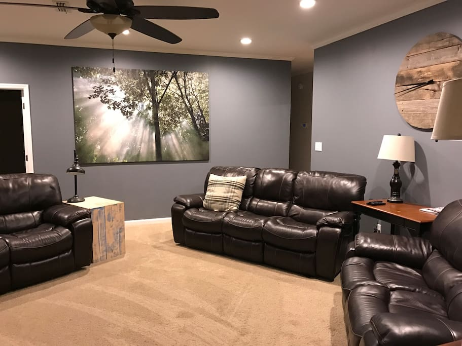 """Open living room with reclining couches and new 65"""" tv"""