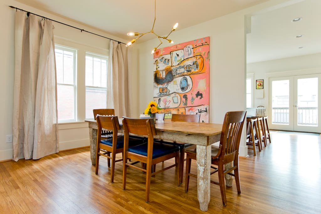Open dining room with farm table and original art by local painter J. Todd Greene