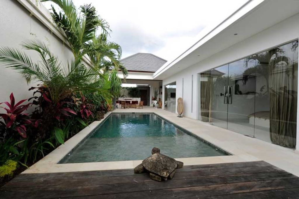 Swimming pool of villa Kallayaan in its tropical garden. On the right, bedrooms. At the bottom, opened living room.