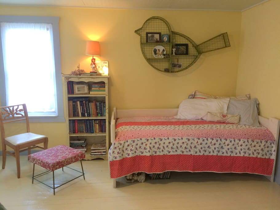 Twin featherbed with toy animals and classic children's books tucked beneath.