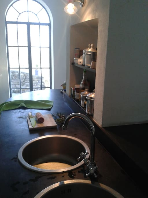 Praktische Küche: Zwei Spülbecken und schneller Zugriff auf Kochutensilien im offenen Regal