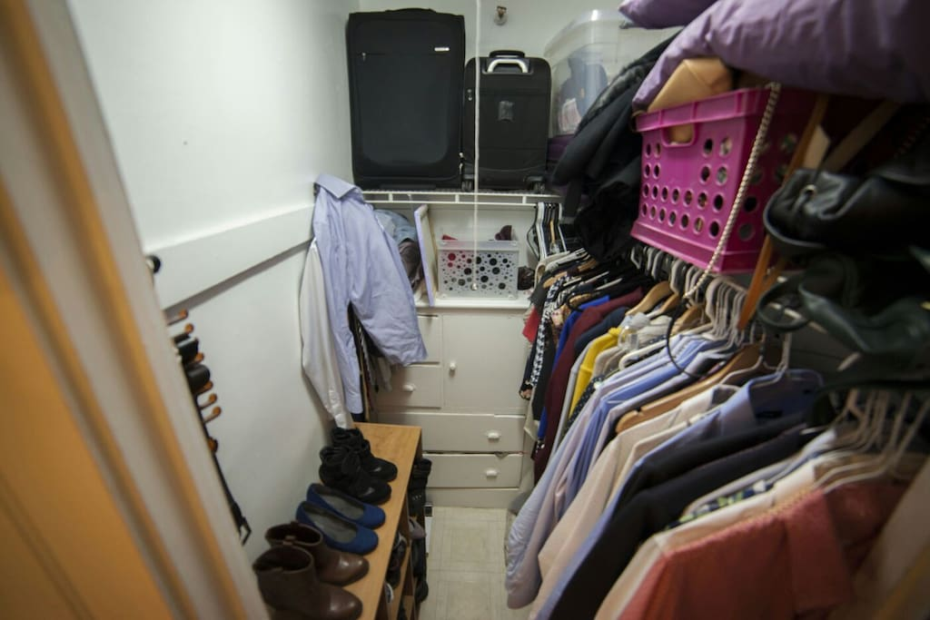 Walk-in closet that fits two people's wardrobes, luggage, and other miscellaneous items
