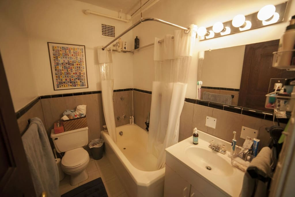 Clean, comfortable bathroom with salon lights and all the essentials