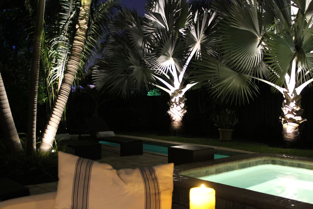 A view of the landscaped garden and pool at night