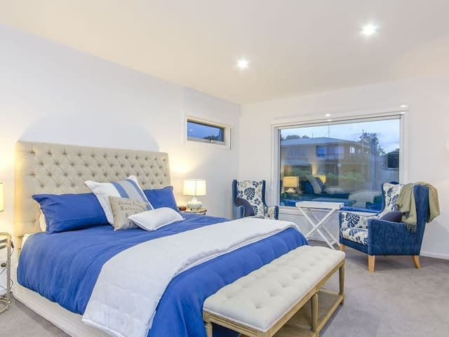 The lavish master bedroom features a plush king bed, ensuite and walk-in robe as well a window-side sitting space.