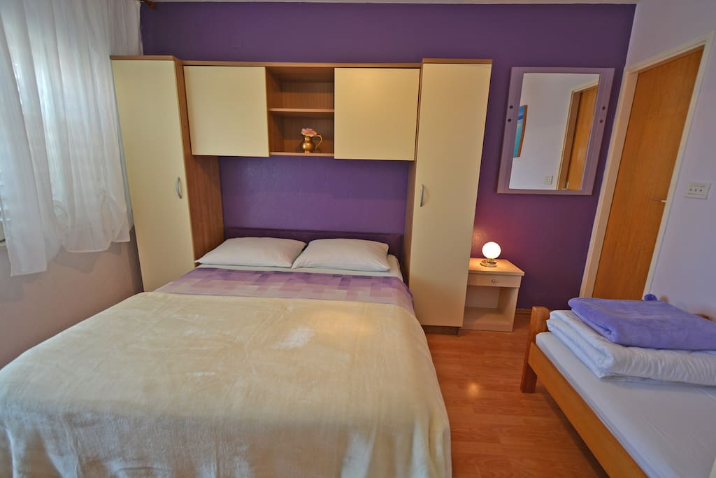 Comfortable Lavender Sky room has large double bed with a single bed, an ensuite shower bathroom and in-room kitchenette with a dining space on a balcony
