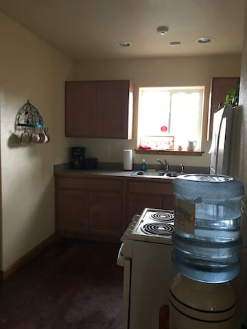 Kitchen- stove, full fridge, microwave, kitchen dishes, pans, silverware, toaster, coffee pot and coffee, sugar, creamer and drinking water.
