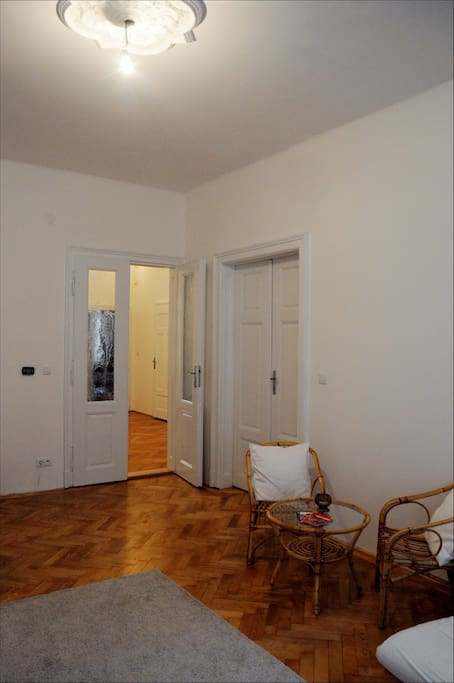 Spacious room with high ceiling and wooden parquet, sofa, two rattan chairs, working desk & rolling -chair.