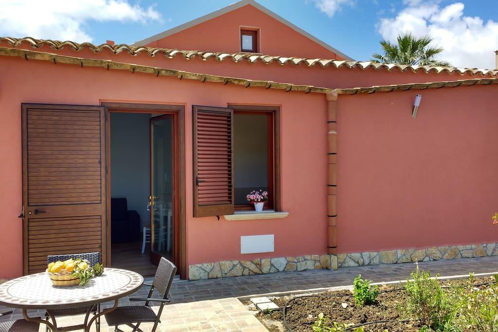 Spazio esterno ad uso esclusivo, dotato di area pavimentata e arredamento da esterni, con vista sull'ingresso dell'alloggio.