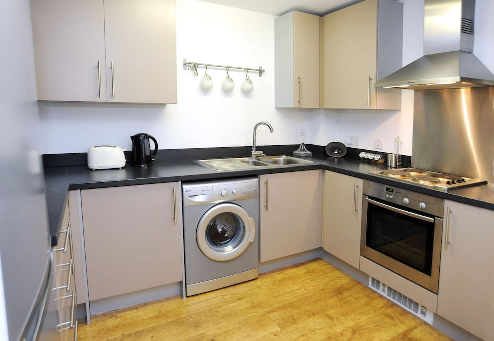 Kitchen, with microwave, washing machine, toaster and kettle.