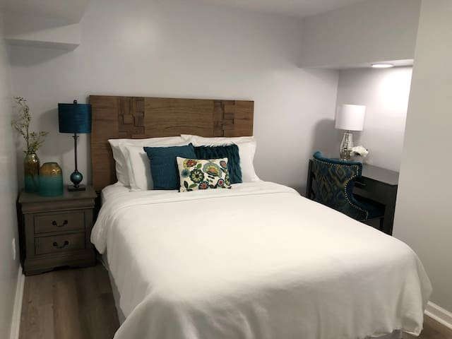 Plush queen sized bed (2nd bedroom of 2) with private workspace and closet.