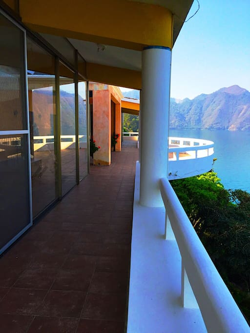 You can walk through an opened hallway the length of the villa with a 360 degree view of the lake, the mountains and the volcanoes .