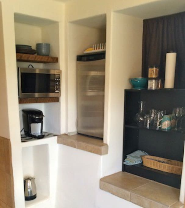 Kitchenette with fridge, microwave and coffee maker.