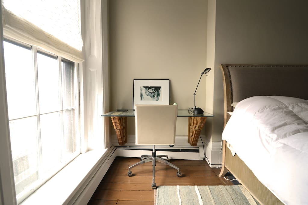 closeup of writing desk, next to bedroom, with view out 6-foot high window to public garden