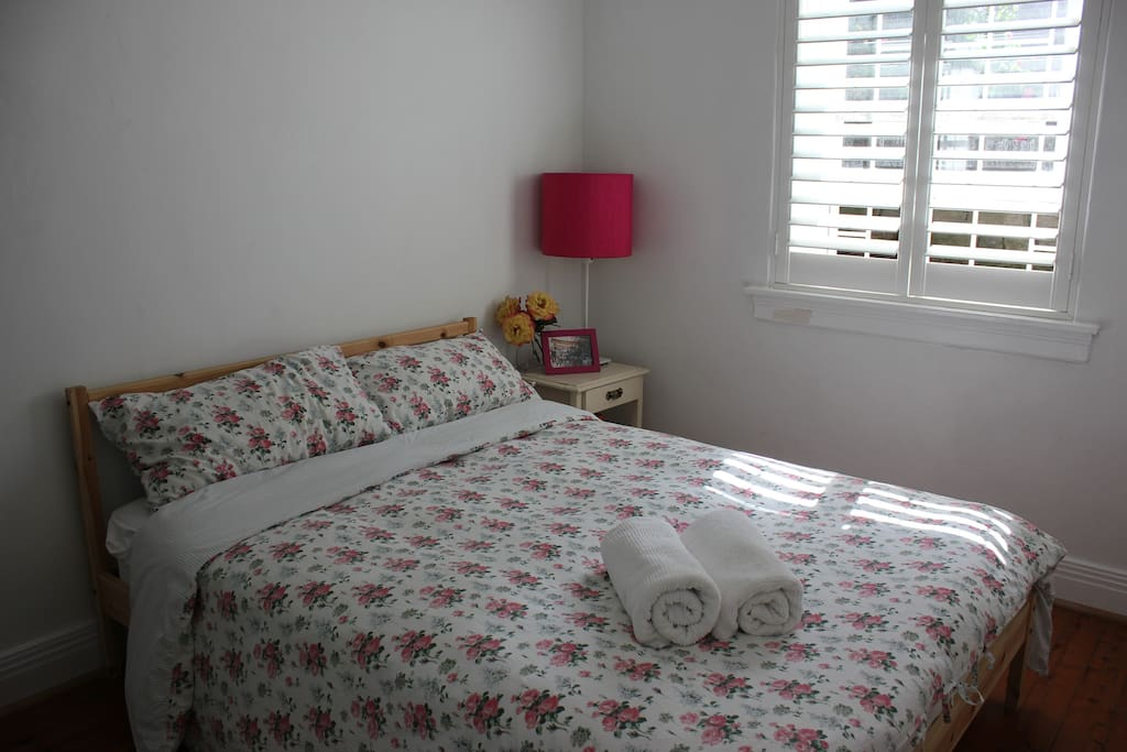 Spacious bedroom with fitted wardrobe, and plantation shutters