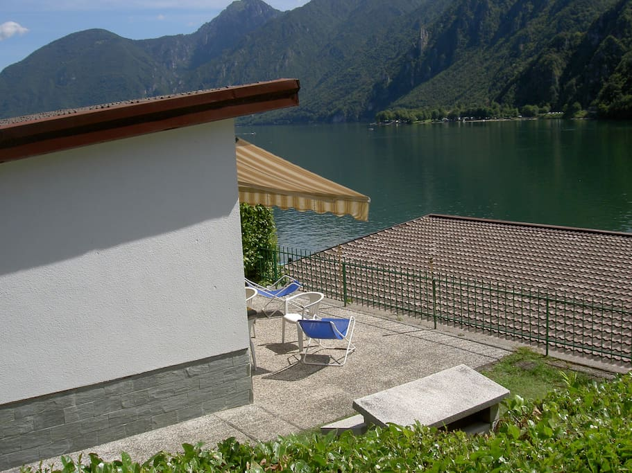 Side view of the house with a large terrace and a beautiful view over Lake Idro.  - Seitenansicht des Hauses auf Ferienpark Tre Capitelli am Idrosee