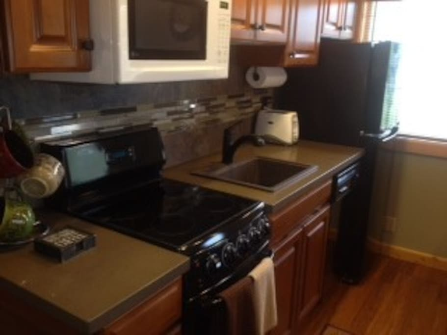 Fully equipped kitchen with new appliances, cookware, and dishes.