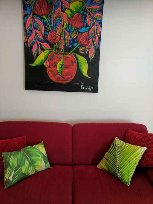 Red couch with tropical art work by local artists.